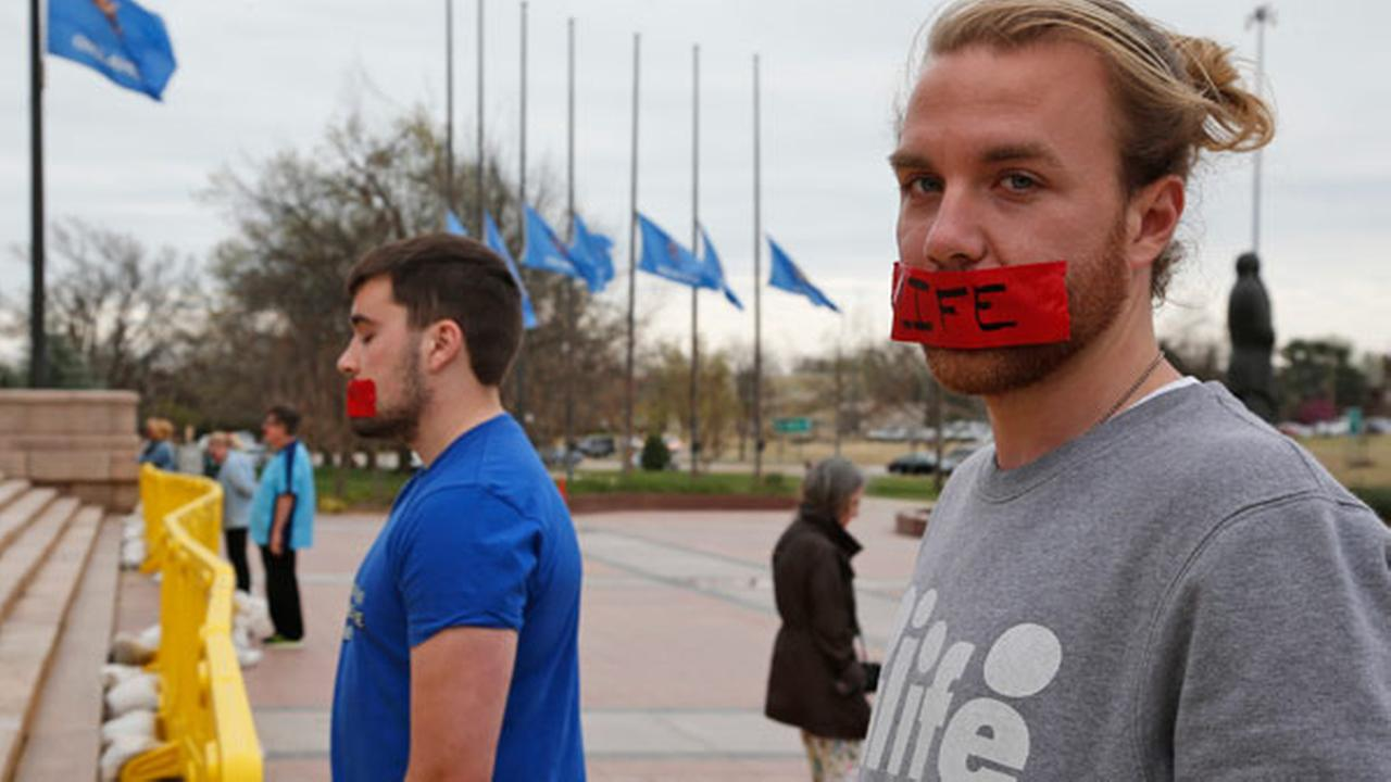 Miles Mitchell, of Edmond, Okla., stands with other members of Bound 4 Life, an anti-abortion group, at the state Capitol in Oklahoma City, Thursday, March 10, 2016.