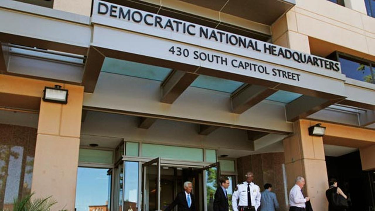 People stand outside the Democratic National Committee (DNC) headquarters in Washington, Tuesday, June 14, 2016.