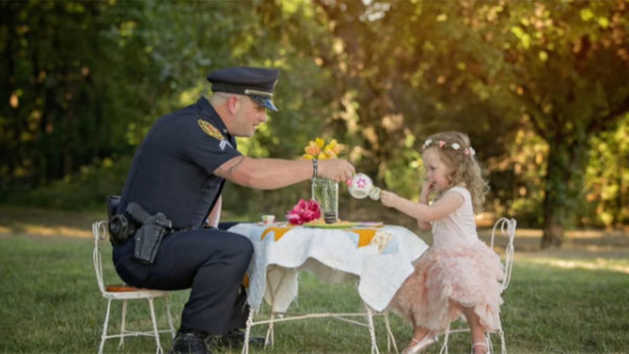 Police officer has tea party with toddler whose life he saved