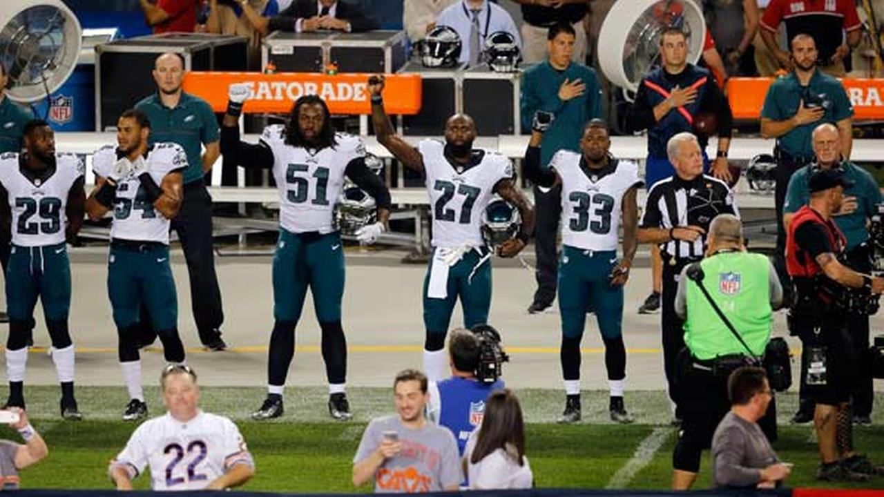 Philadelphia Eagles defensive end Steven Means (51), strong safety Malcolm Jenkins (27) and defensive back Ron Brooks (33) raise their arms during the national anthem.