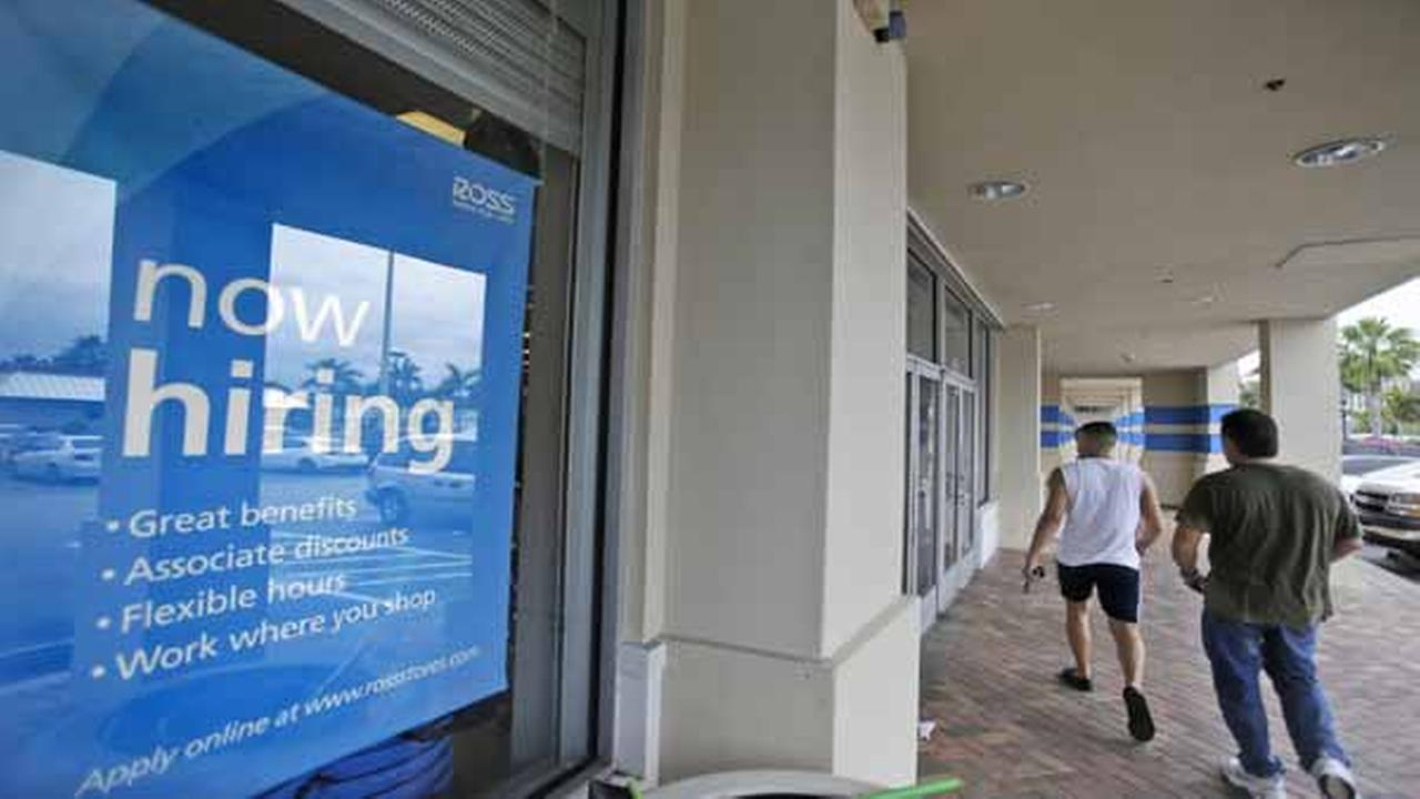 FILE - In this May 16, 2014 file photo, shoppers walk past a now hiring sign at a Ross store in North Miami Beach, Fla.