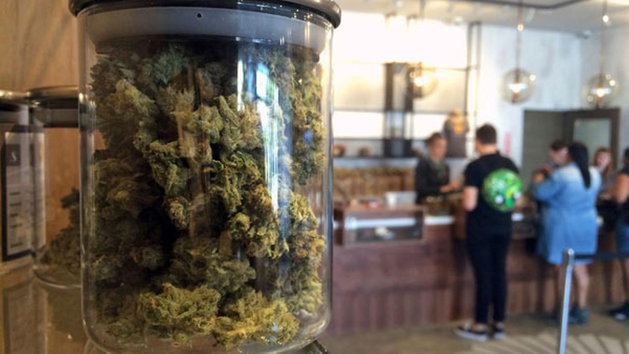 File - In this April 20, 2016 file photo, customers buy products at the Harvest Medical Marijuana Dispensary in San Francisco.