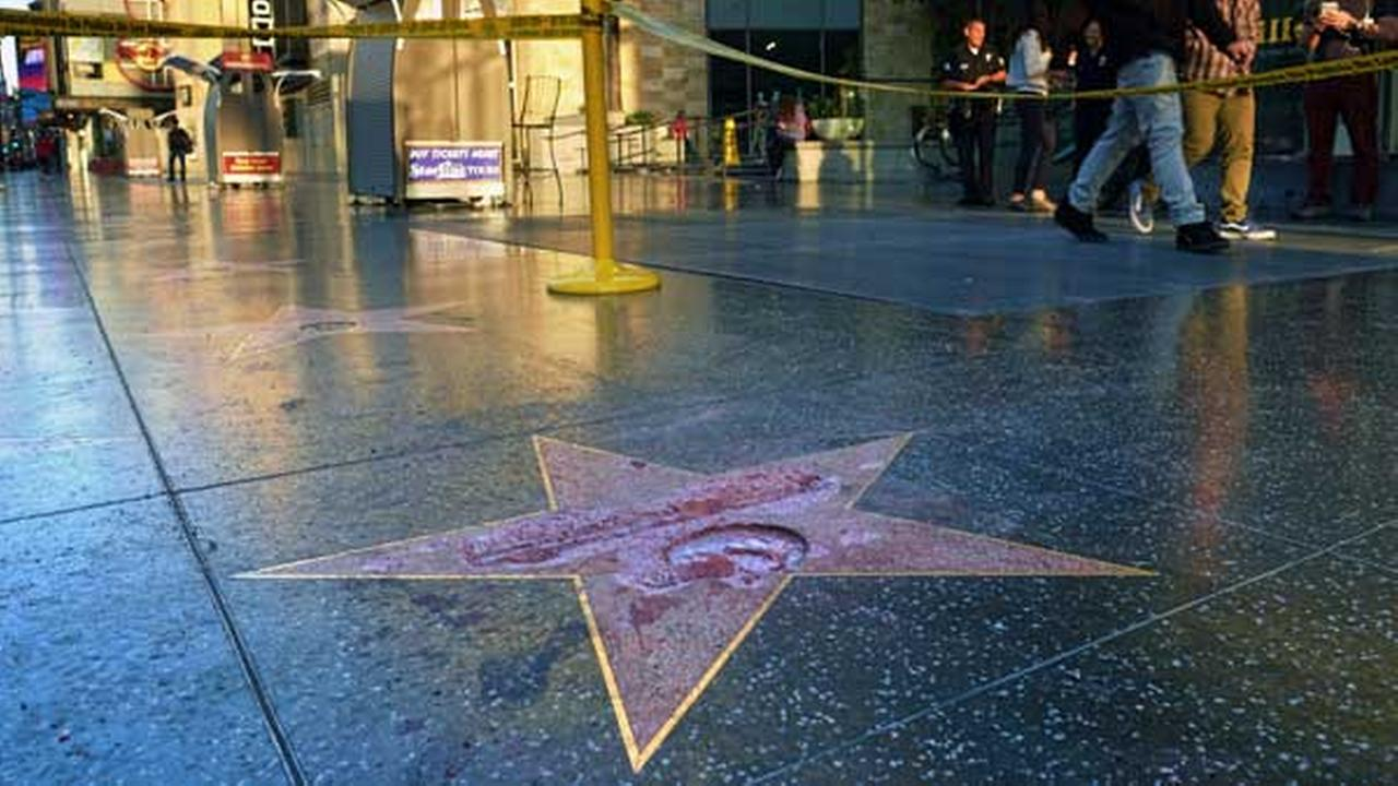 Pedestrians walk past a cordoned off area surrounding the vandalized star for Republican presidential candidate Donald Trump on the Hollywood Walk of Fame, Wednesday, Oct. 26,2016,