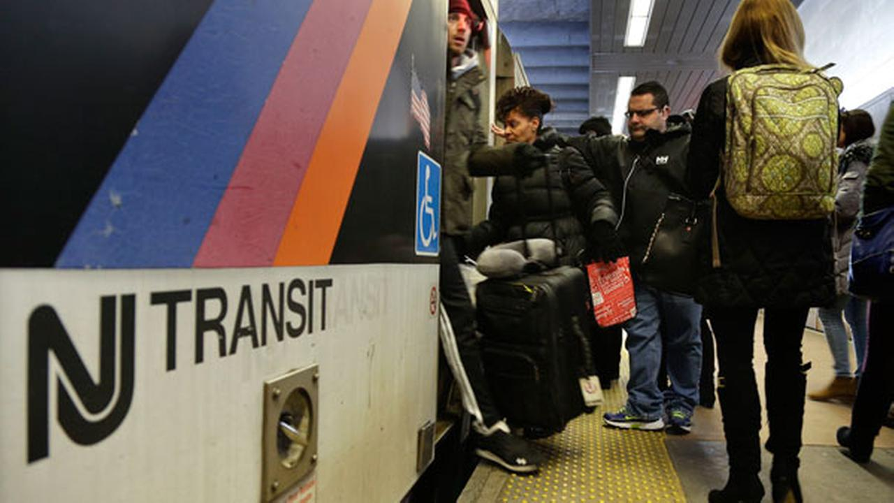 FILE - In this March 4, 2016 file photo, New Jersey Transit passengers board a train at Seacaucus Junction in Seacaucus, N.J.