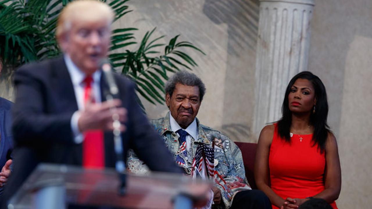 Omarosa Manigault, right, and boxing promoter Don King, center, listen as Republican presidential candidate Donald Trump speaks to the Pastors Leadership Conference.