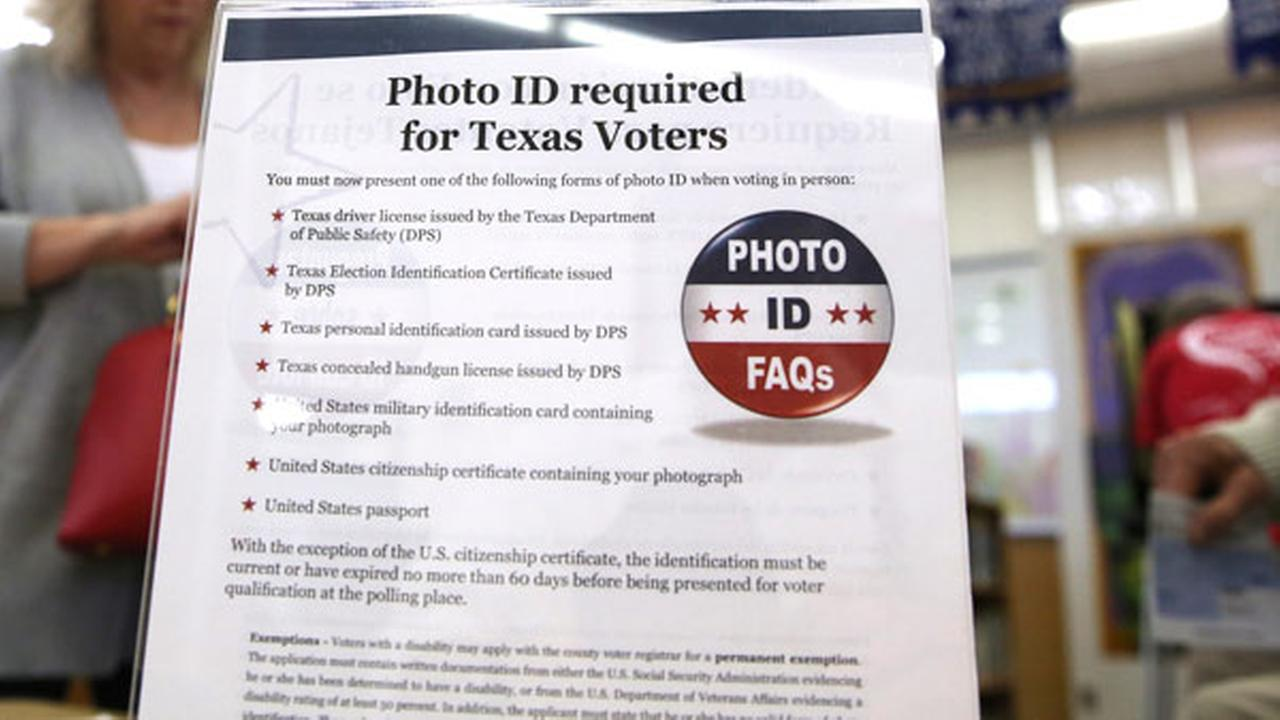 FILE - In this March 1, 2016, file photo, a sign tells voters of voter ID requirements before participating in the primary election at Sherrod Elementary school in Arlington, Texas