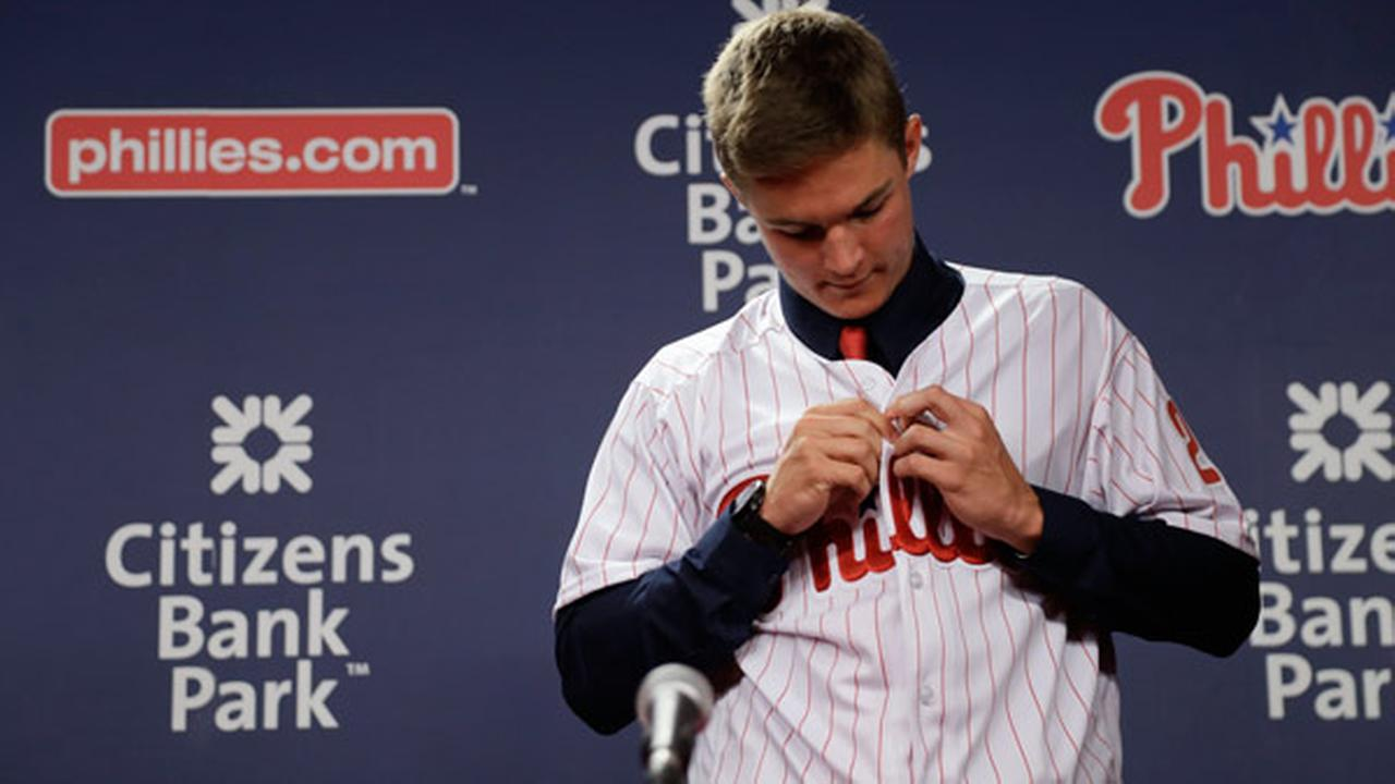Mickey Moniak, the Philadelphia Phillies first overall selection in 2016 MLB draft, puts on his jersey during a baseball news conference at Citizens Bank Park.