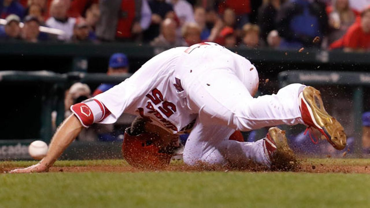 St. Louis Cardinals Stephen Piscotty falls after being hit in the head with the ball while scoring during the fifth inning.