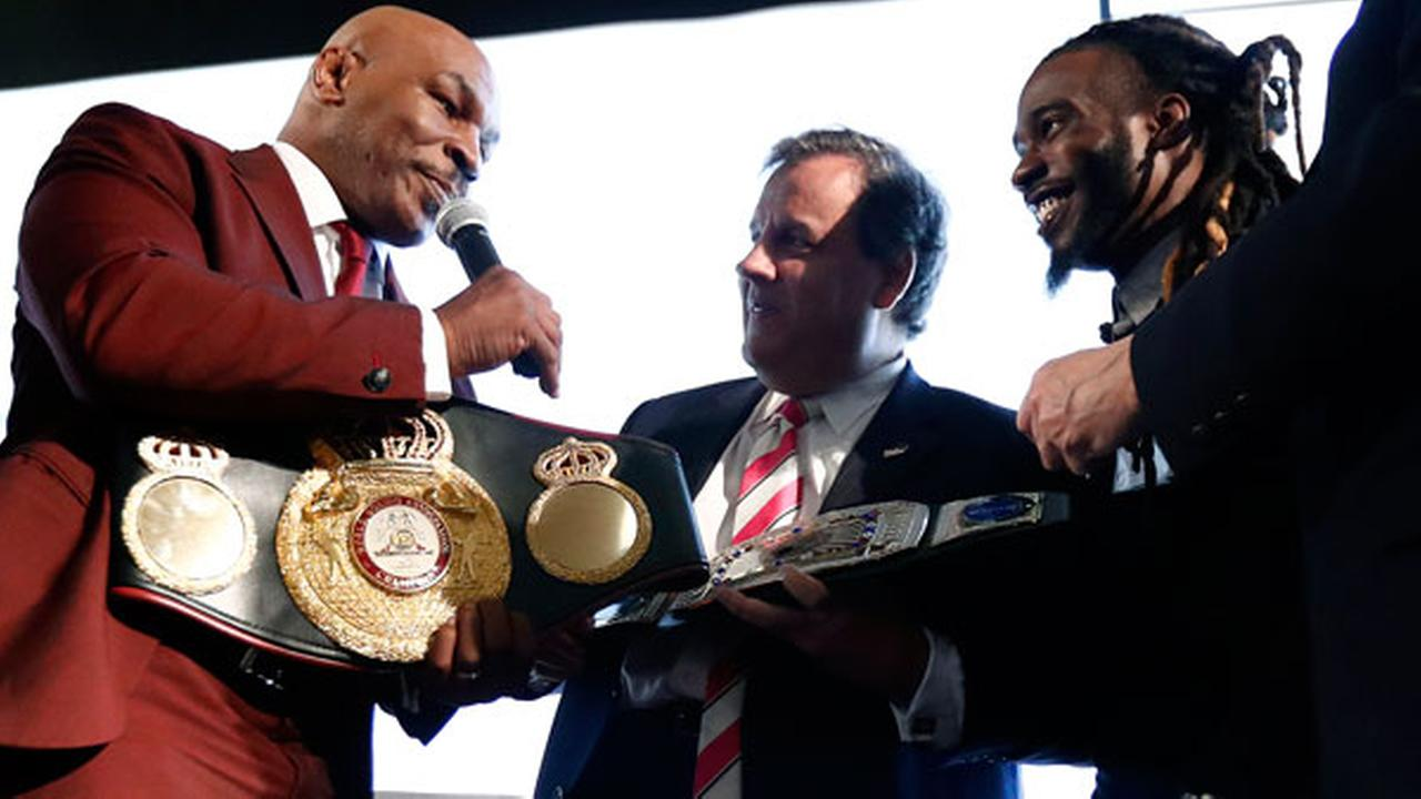 New Jersey Gov. Chris Christie, center, is presented with a belt by boxer Mike Tyson, left, for Christies work in promoting help for ex-prisoners re-entering society.