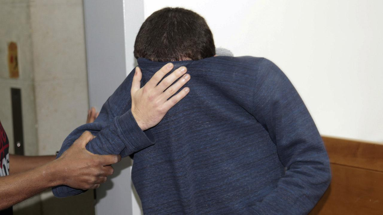 An 18-year-old dual U.S.-Israeli citizen covers his face as he is brought to court in Rishon Lezion, Israel, Thursday, March 23, 2017.