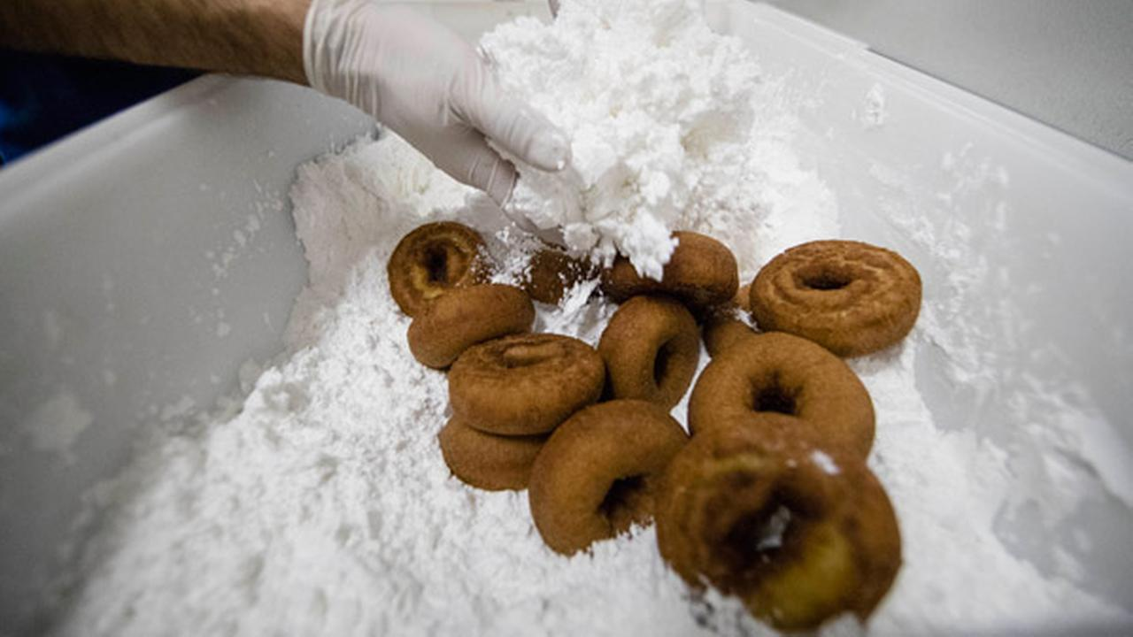In this Wednesday, July 26, 2017 photo, Chef Matt Fein applies powder sugar to donuts for a Phish concert, at Federal Donuts in Philadelphia.
