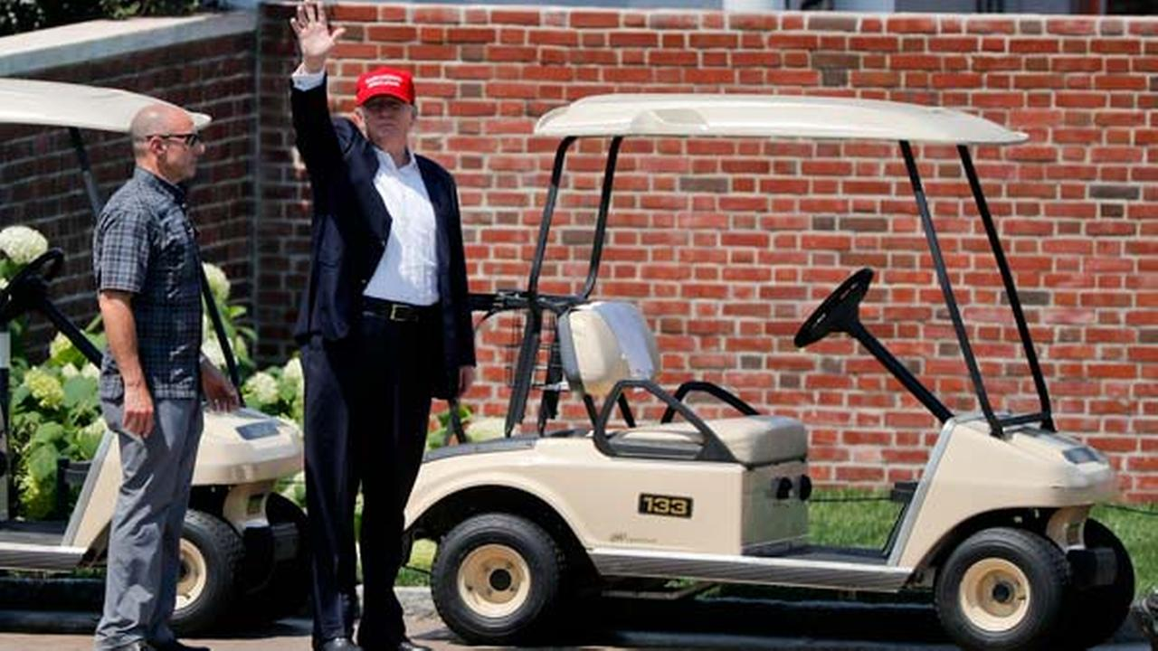 President Donald Trump waves to spectators as he walks out of his residence at the Trump National Golf Club during the third round of the U.S. Womens Open Golf tournament Saturday