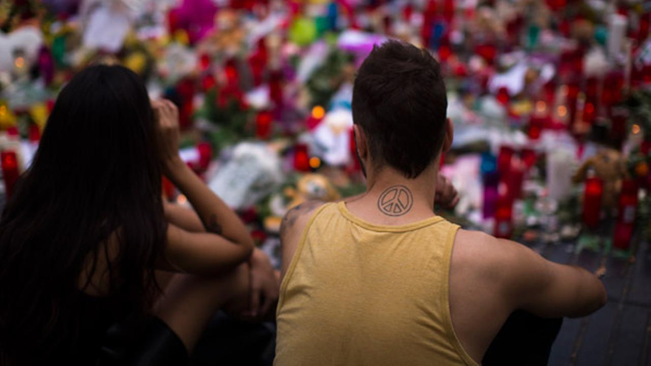 People sit next to candles and flowers placed on the ground after a terror attack that killed 14 people and wounded over 120 in Barcelona, Spain, Sunday, Aug. 20, 2017.