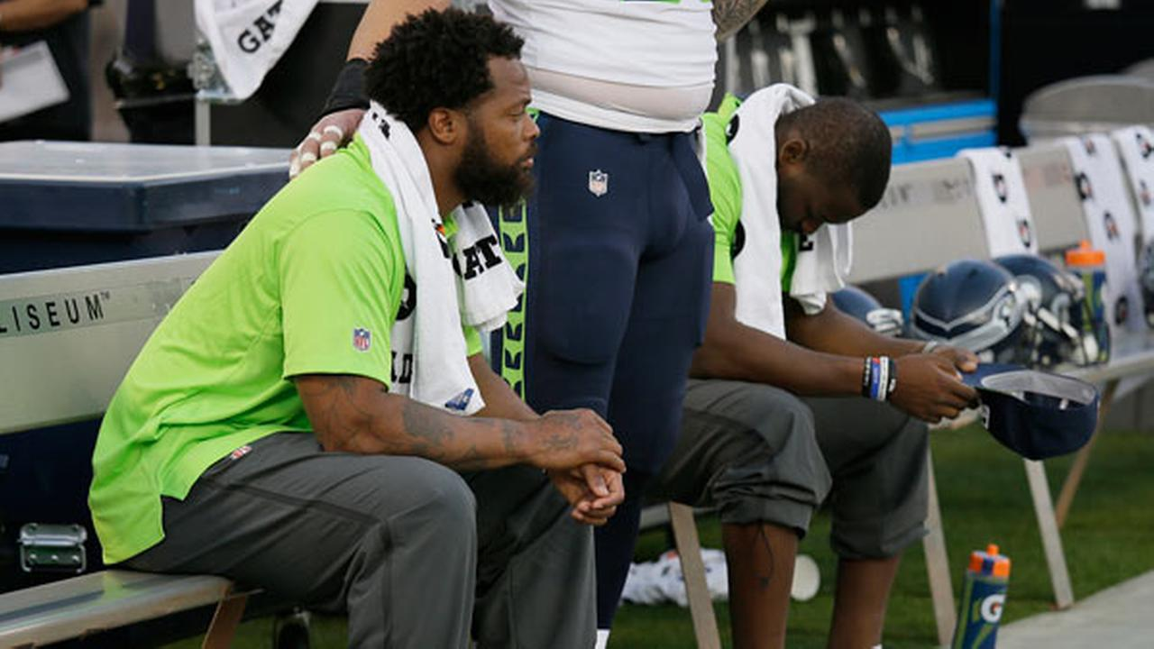 FILE - This Thursday, Aug. 31, 2017 file photo Seattle Seahawks defensive end Michael Bennett, left, sits during the playing of the national anthem.