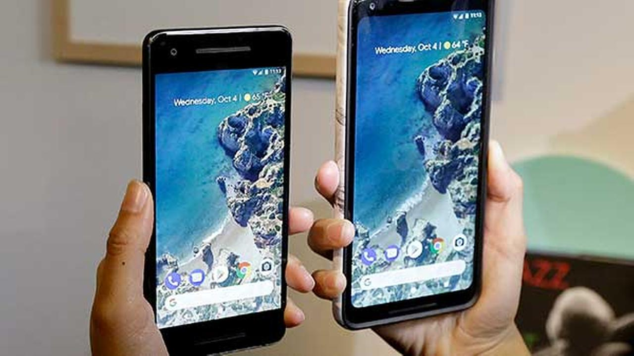 A woman holds up the Google Pixel 2 phone, left, next to the Pixel 2 XL phone at a Google event at the SFJAZZ Center in San Francisco, Wednesday, Oct. 4, 2017.