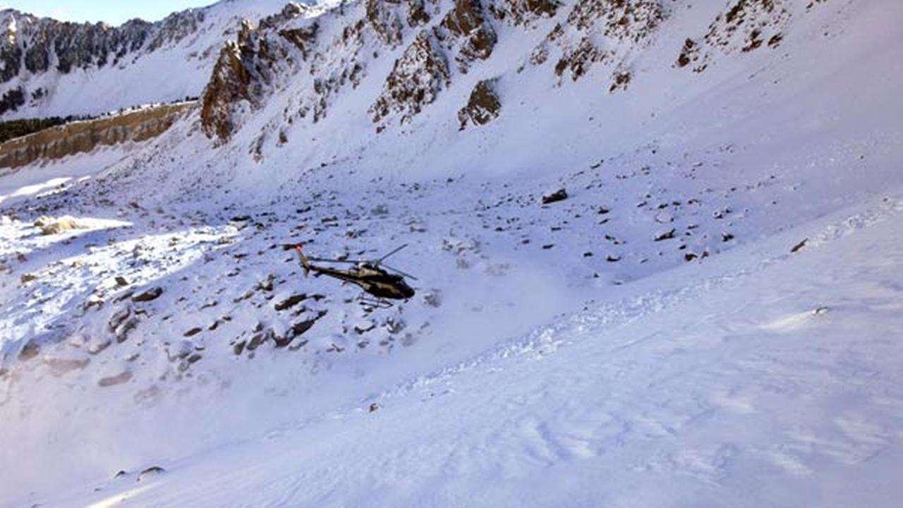In this Monday, Oct. 9, 2017, photo provided by the The Gallatin National Forest Avalanche Center, a helicopter searches an avalanche debris field for a missing skier on Imp Peak.