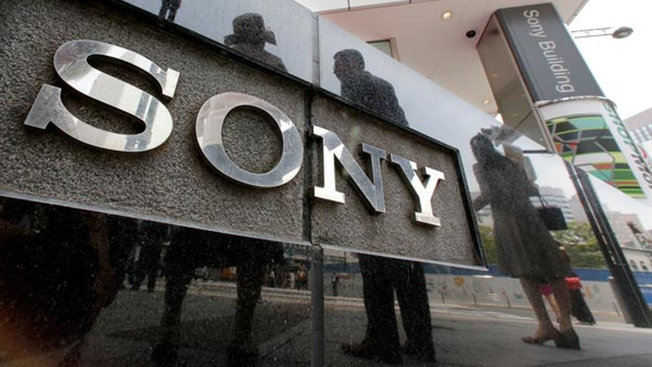 People are reflected on a wall of the Sony building at Ginza shopping district in Tokyo, Wednesday, May 14, 2014.