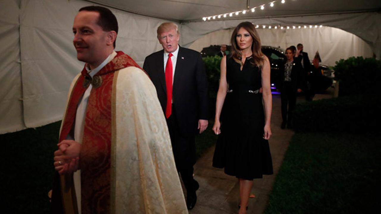 President Donald Trump and first lady Melania, escorted by Rev. James R. Harlan, as they arrive for Christmas Eve service at the Church of Bethesda-by-the-Sea in West Palm Beach.