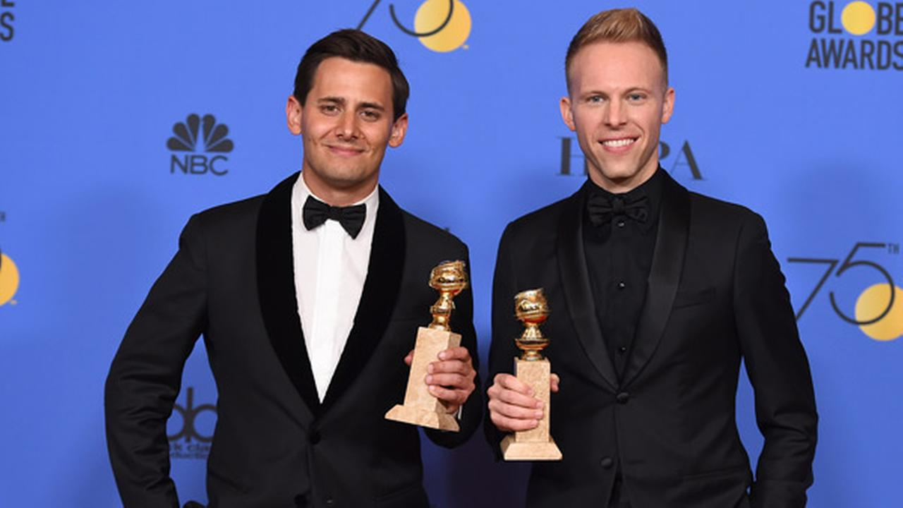 Benj Pasek, left, and Justin Paul pose in the press room with the award for best original song - motion picture for This Is Me from The Greatest Showman.