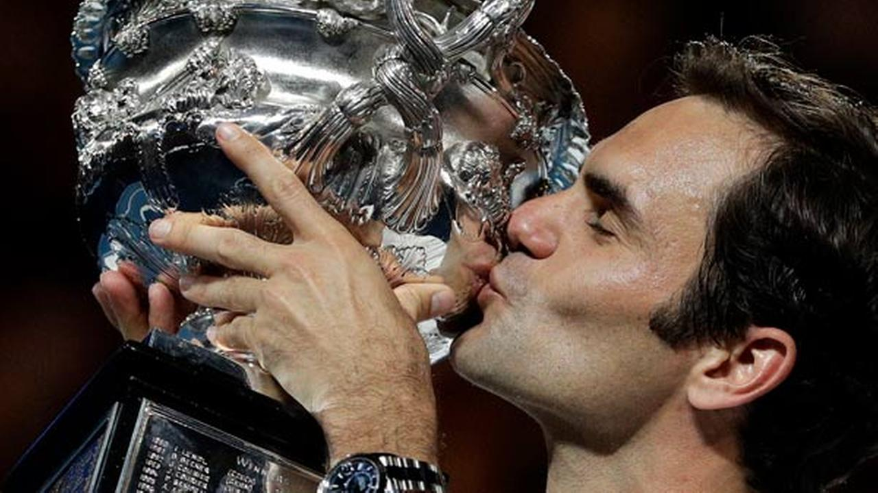 Switzerlands Roger Federer holds his trophy aloft after defeating Croatias Marin Cilic during the Australian Open championships in Melbourne, Australia, Sunday, Jan. 28, 2018.