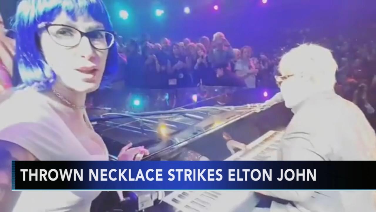 Fan throws Mardi Gras beads at Elton John during performance