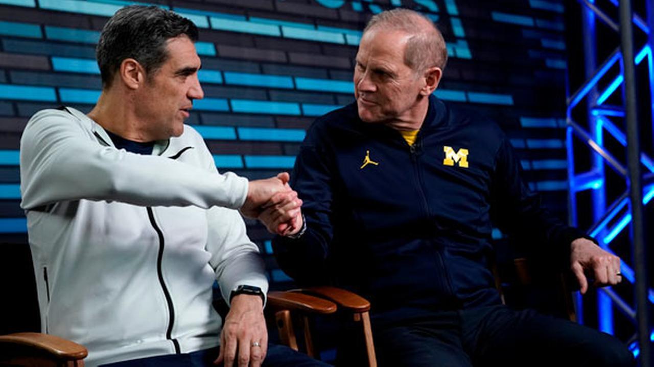 Villanova head coach Jay Wright, left, and Michigan head coach John Beilein shake hands during an interview for CBS Sports Network.