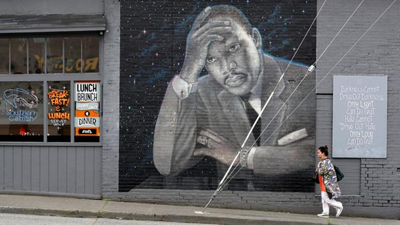 A woman walks past a large mural of the Rev. Martin Luther King Jr. on the side of a diner, painted by artist James Crespinel in the 1990s, Tuesday, April 3, 2018.