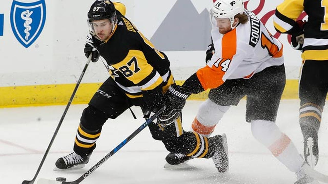 Pittsburgh Penguins Sidney Crosby (87) works the puck around Philadelphia Flyers Sean Couturier (14) during the third period of an NHL hockey game, Sunday, March 25, 2018.