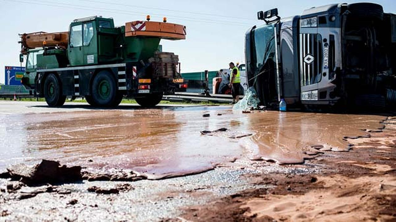 Tons of liquid milk chocolate are spilled and block six lanes on a highway after a truck transporting it overturned near Slupca, in western Poland, on Wednesday, May 9, 2018.