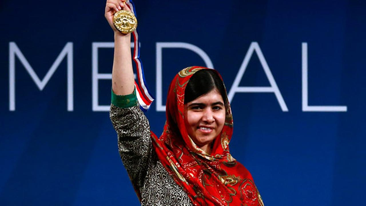 Malala Yousafzai holds up her Liberty Medal during a ceremony at the National Constitution Center, Tuesday, Oct. 21, 2014, in Philadelphia.