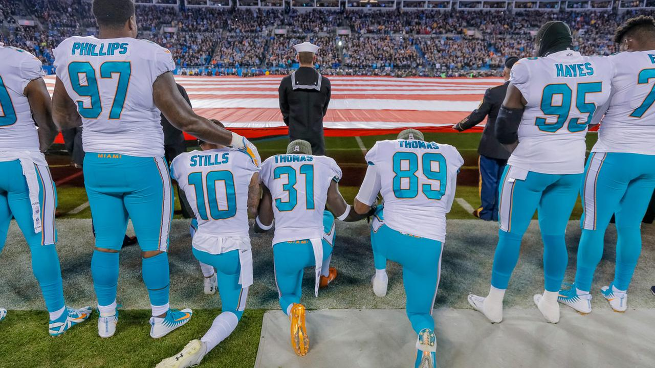 Miami Dolphins  Kenny Stills (10), Michael Thomas (31) and Julius Thomas (89) kneel before an NFL football game against the Carolina Panthers in Charlotte, N.C., Nov. 13, 2017.