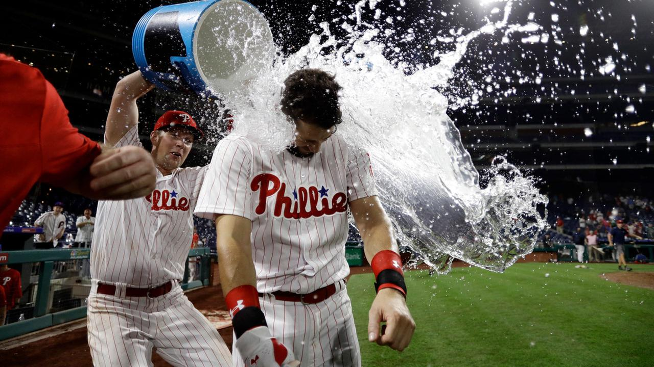 Philadelphia Phillies Trevor Plouffe, center, is doused by Rhys Hoskins after Plouffes game-winning three-run home run off Los Angeles Dodgers relief pitcher Kike Hernandez.