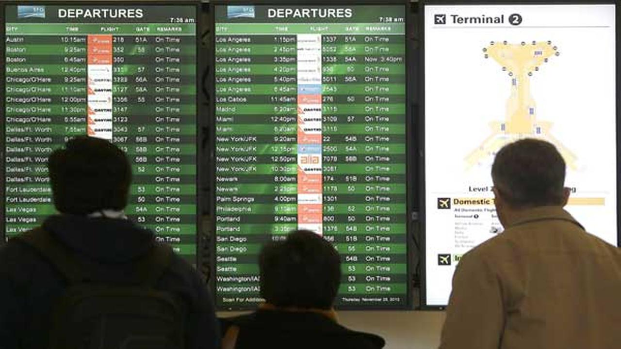 A group looks at the departures board in the domestic terminal at San Francisco International Airport in San Francisco, Thursday, Nov. 28, 2013.