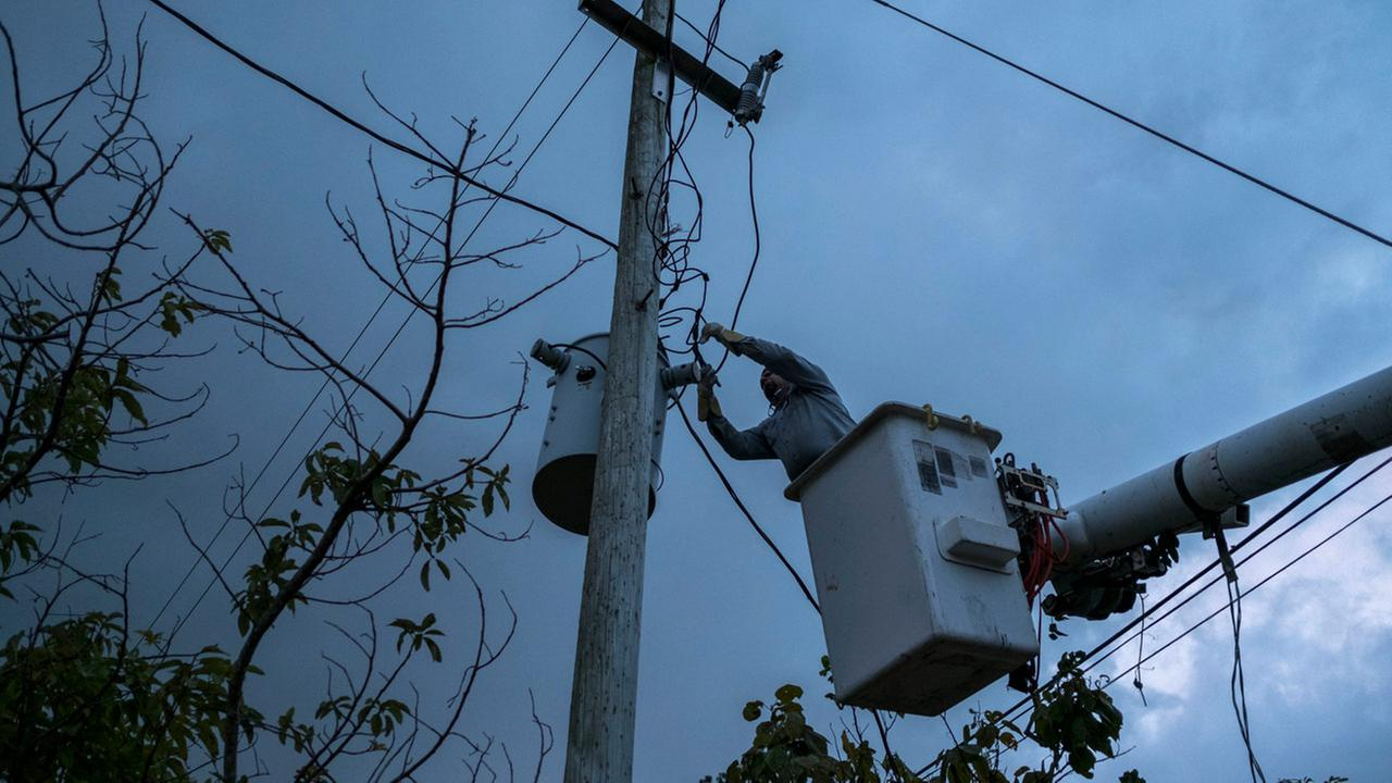 In this July 12, 2018 photo, a laborer from the Puerto Rico Power Authority works to restore power in Adjuntas, Puerto Rico.
