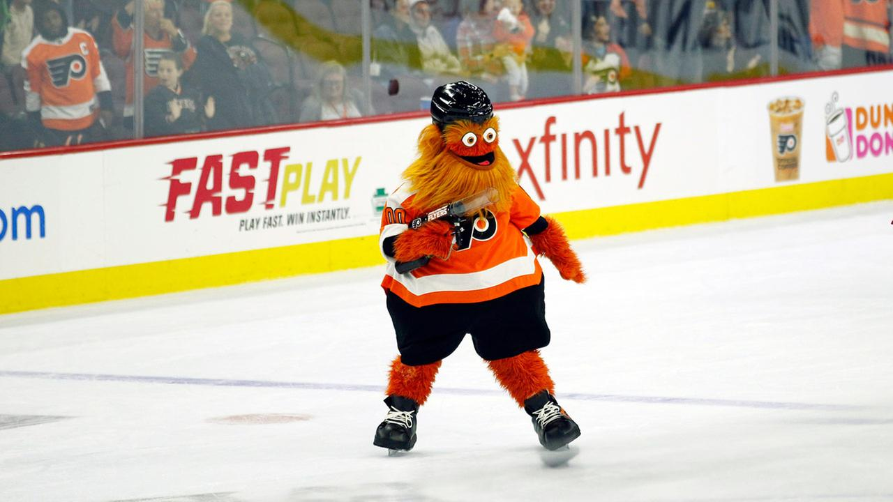 The Philadelphia Flyers mascot, Gritty, shoots T-shirts into the crowd during the second intermission of the Flyers preseason NHL hockey game against the Boston Bruins.