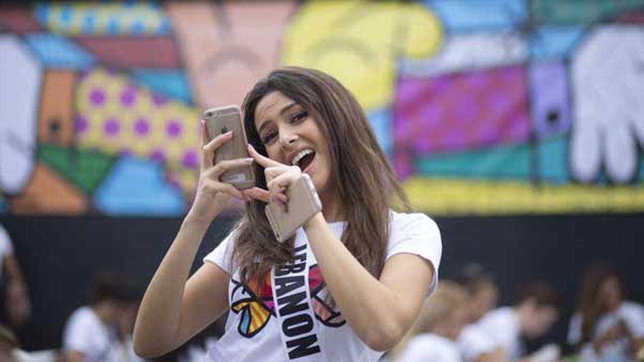 FILE - In this Sunday, Jan. 11, 2015 file photo, Miss Lebanon, Saly Greige, poses for photos after she painted on a wall in Miamis Wynwood area.