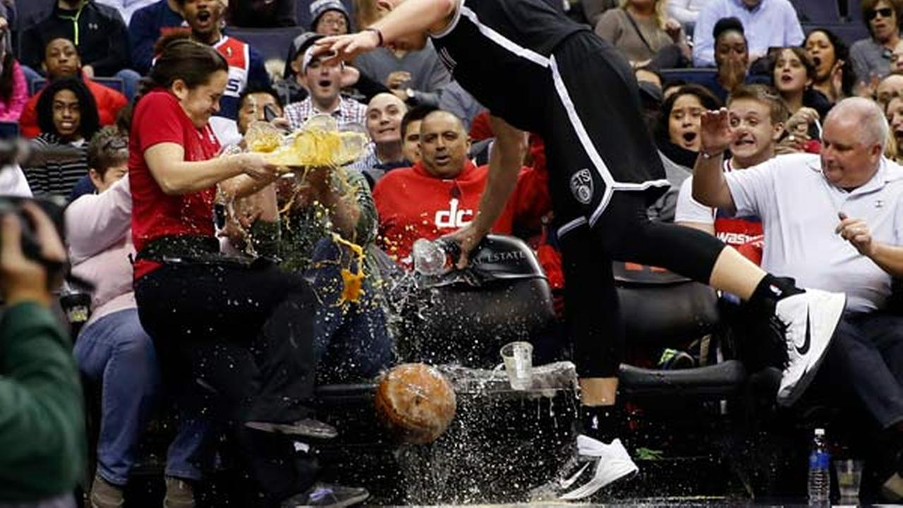 Waitress Deila Barr looses a tray of beers as Brooklyn Nets center Mason Plumlee (1) runs into her chasing the ball in the first half of an NBA basketball game.