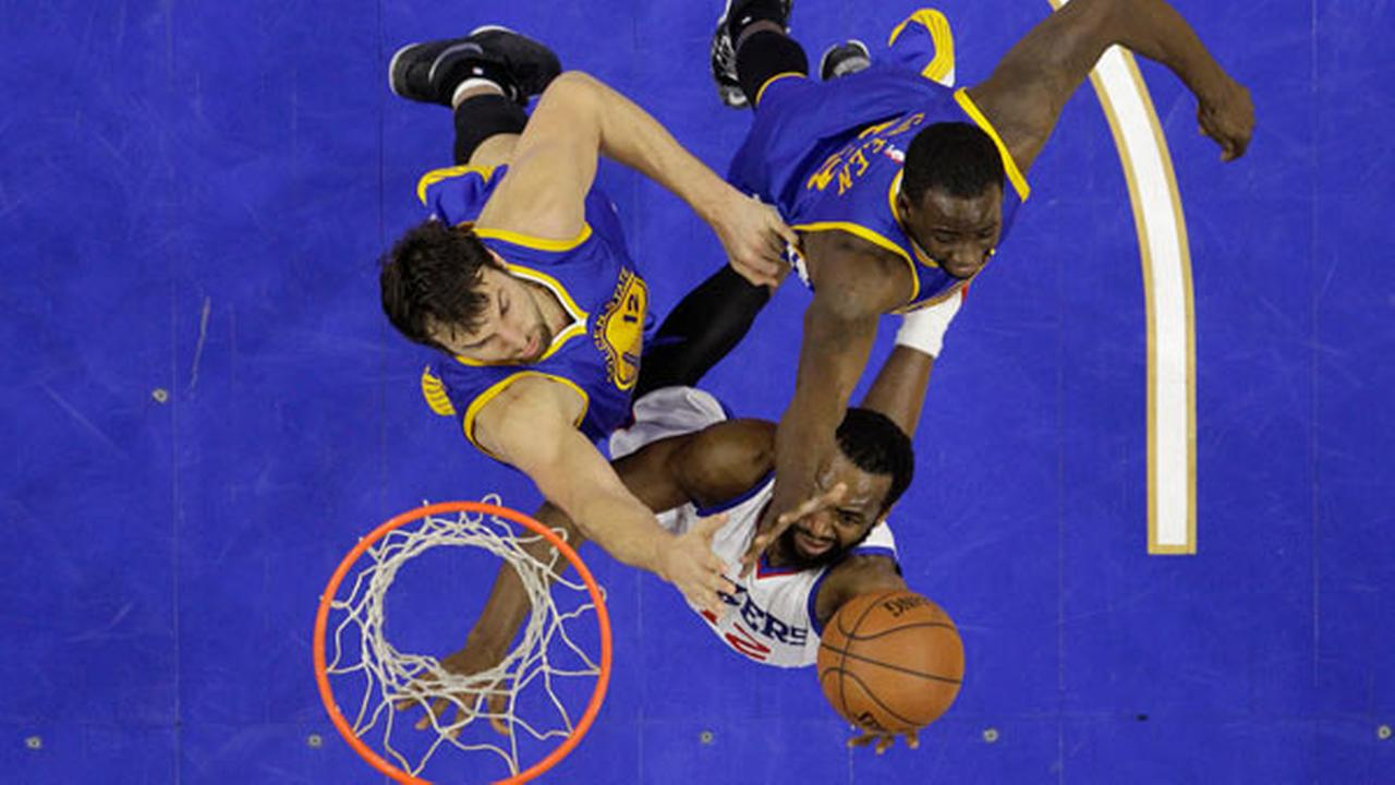 Philadelphia 76ers Luc Mbah a Moute, bottom, of Cameroon, goes up for a shot against Golden State Warriors Andrew Bogut, left, of Australia, and Draymond Green