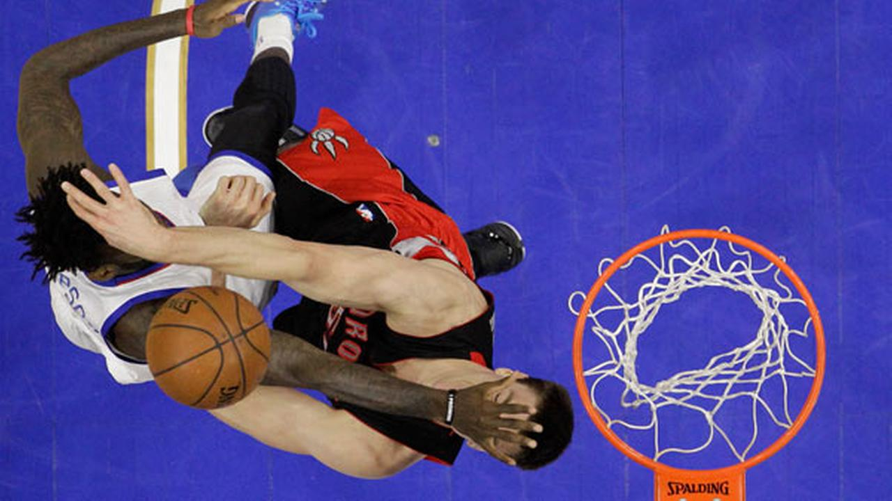 Toronto Raptors Tyler Hansbrough, right, blocks a shot by Philadelphia 76ers JaKarr Sampson during the second half of an NBA basketball game, Monday, March 2, 2015, in Philadelph