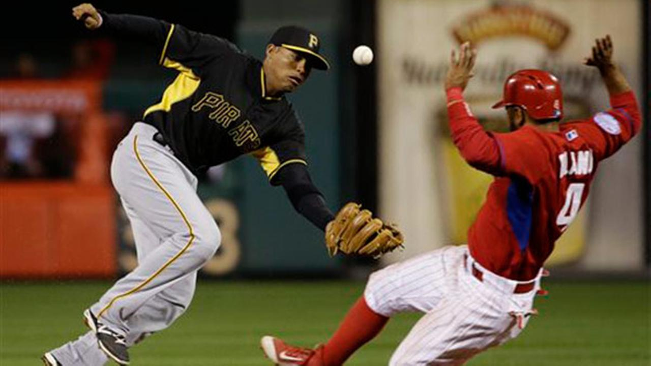 Pittsburgh Pirates shortstop Gustavo Nunez, left, tries to catch a wild throw as Philadelphia Phillies Andres Blanco steals second base Friday, April 3, 2015, in Philadelphia.