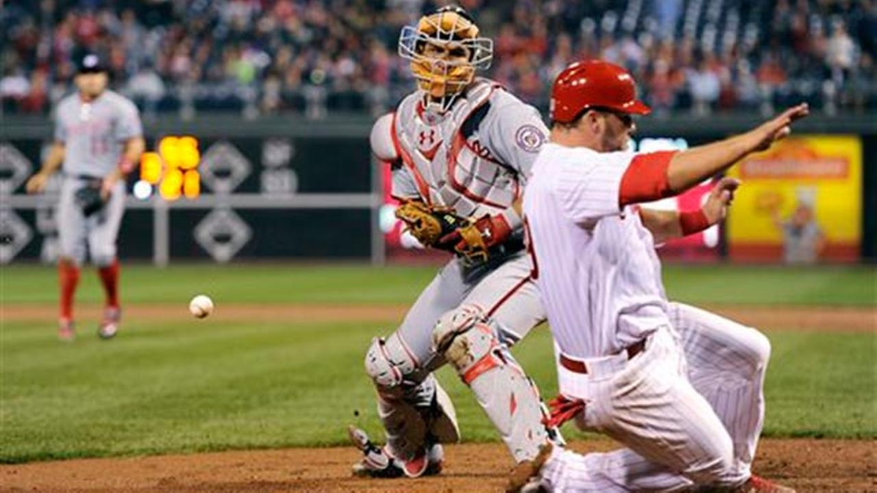 Phillies Cameron Rupp slides past Washington Nationals catcher Wilson Ramos and scores on a Cesar Hernandez single to right field, Friday, April 10, 2015, in Philadelphia.