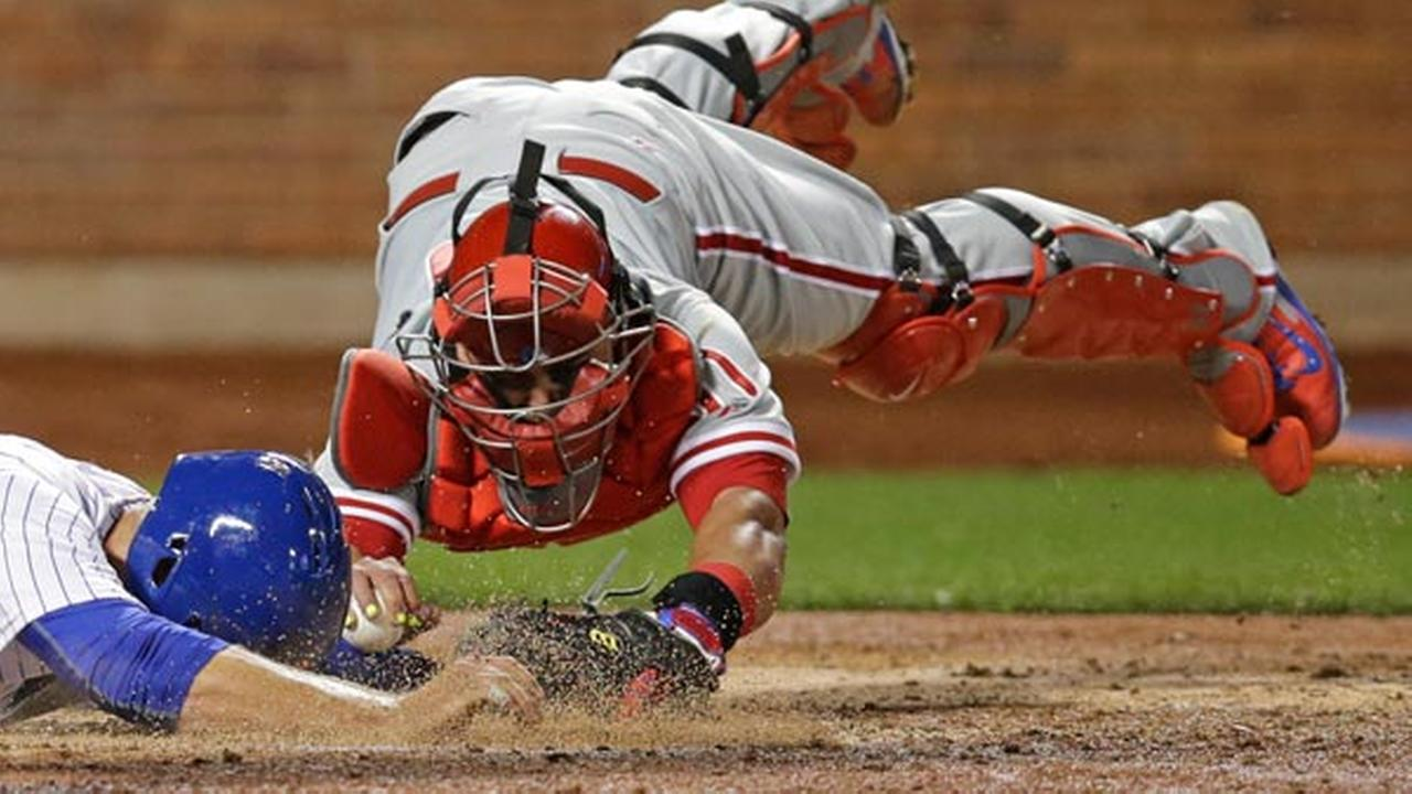 Philadelphia Phillies catcher Carlos Ruiz dives while trying to tag New York Mets Lucas Duda, who returned to the plate after failing to tag it during the fifth inning.