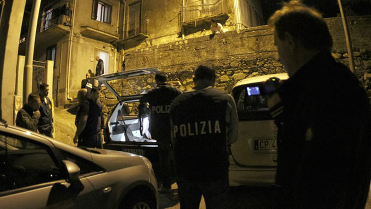Police officers stand outside a suspects house during an operation conducted with U.S. FBI agents, in Sinopoli, southern Italy, early Thursday morning, May 7, 2015.