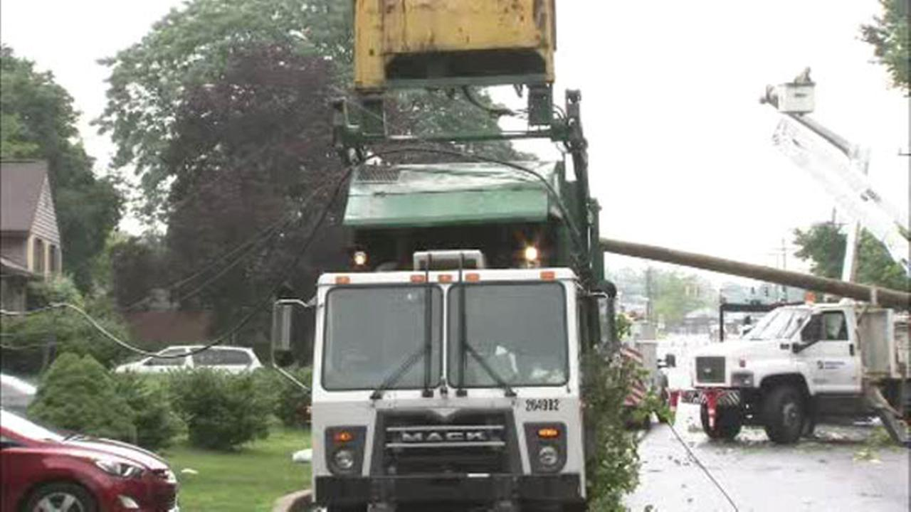 A trash truck traveling with its bucket in the raised position caught wires overhead bringing down a utility pole in Wilmington.