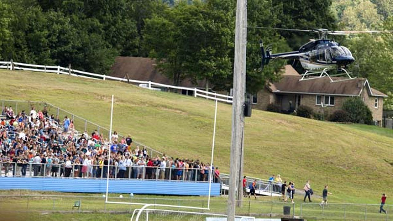 A West Virginia State Police helicopter lands on the football field at Philip Barbour High School in Philippi, W.V., where students wait on the football field bleachers.