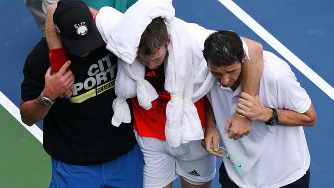 Jack Sock is helped off the court after collapsing during play against Ruben Bemelmans, of Belgium during the second round of the U.S. Open tennis tournament.