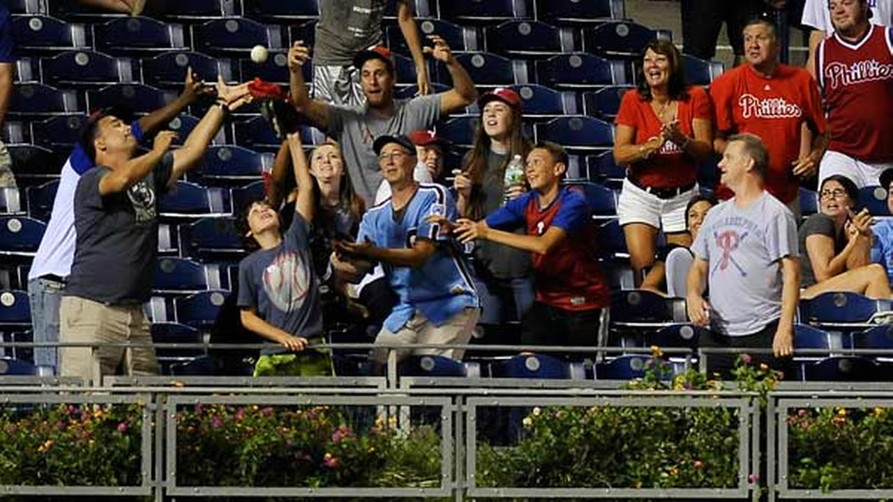 Fans reach for a home run ball hit by Atlanta Braves Hector Olivera in the ninth inning of a baseball game, Monday, Sept. 7, 2015, in Philadelphia.