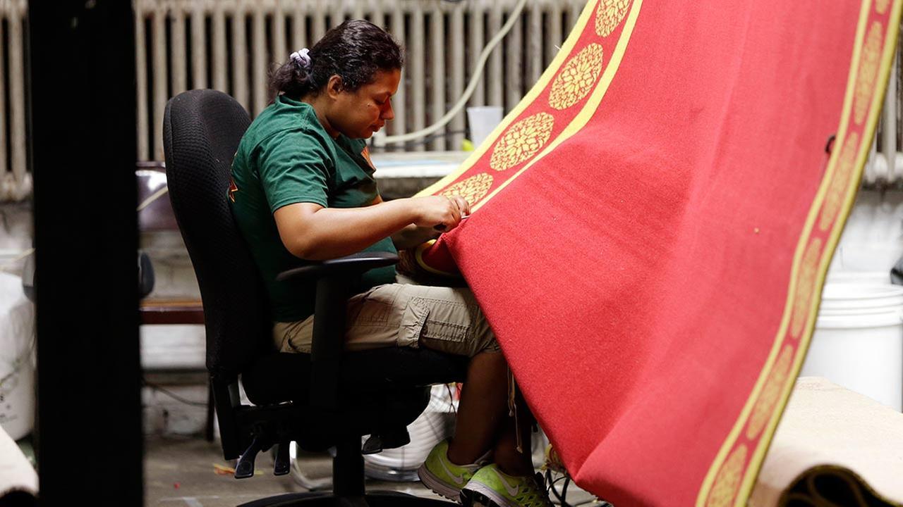 Burler Carmen Martinez works on a carpet made for Pope Francis scheduled visit to Philadelphia, Thursday, Sept. 10, 2015