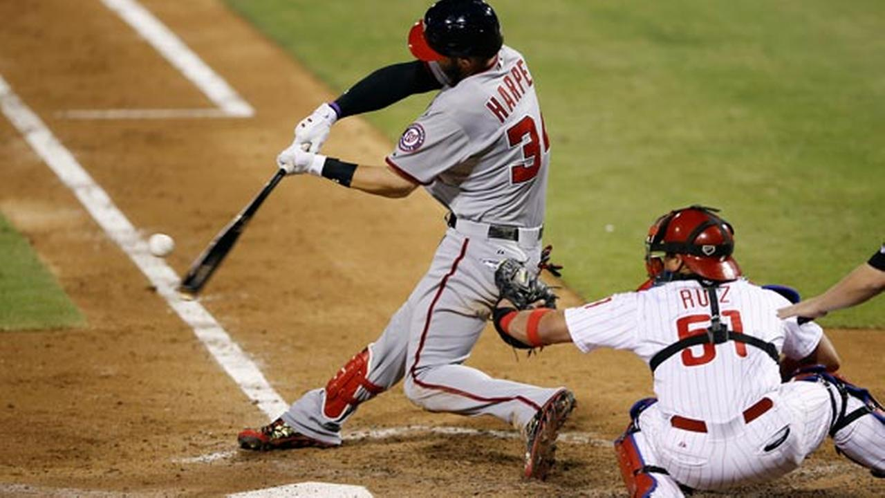 Washington Nationals Bryce Harper, left, hits a two-run home run off Philadelphia Phillies relief pitcher Adam Loewen.