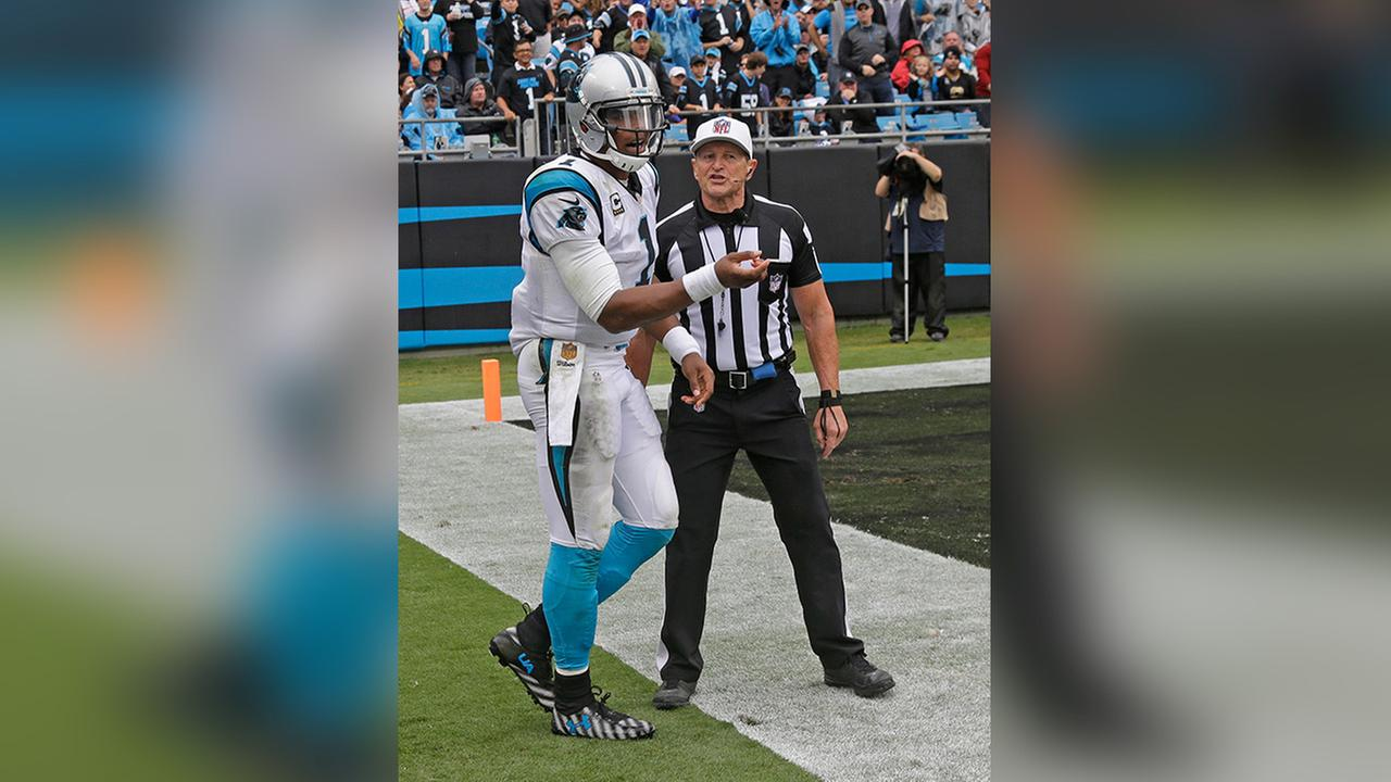 Sept. 27, 2015 photo of Carolina Panthers Cam Newton, left, talks with referee Ed Hochuli, right, after being hit on the sidelines in the second half